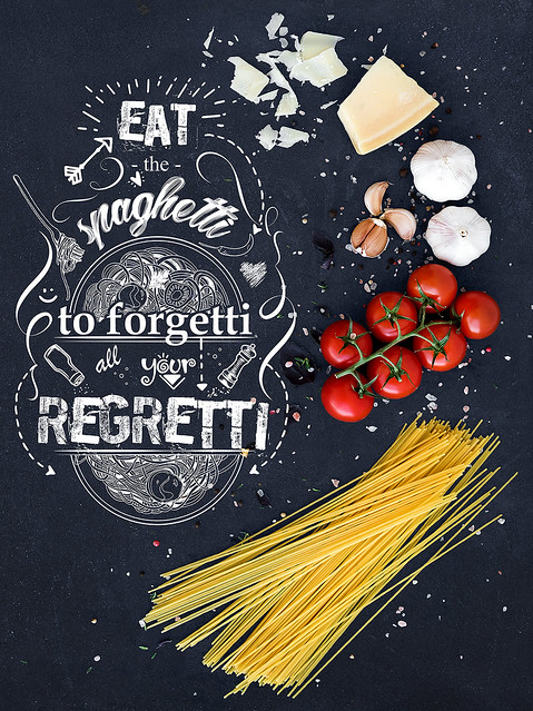 Food frame. Pasta ingredients. Cherry-tomatoes, spaghetti pasta, garlic, basil, parmesan and spices on dark grunge backdrop, copy space