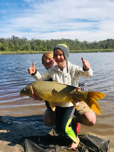 Boy holding a large carp he caught