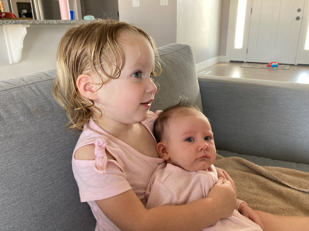 My two-year-old daughter Maggie on the couch, holding here six-week-old sister Olive. Maggie is watching TV off camera, looking over the baby's head