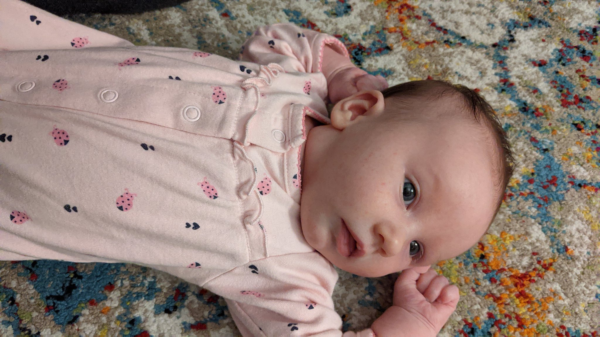 My six-week-old daughter Olive stretching her arms above her head, wearing pink footie pajamas