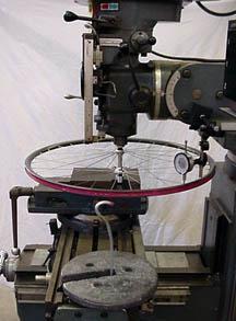 ホイールを固定しリムのたわみを測定した実験器具。重りを引っ掛けて、ダイヤル測定器で測定する。 photo: sheldonbrown