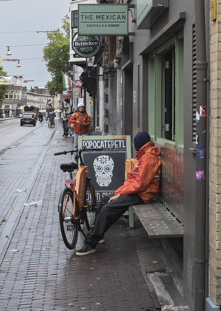 Delivery worker waits for the rain to stop