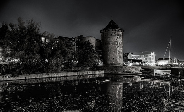 Black and white night view of the Stągiewna Gate Milk Stągwie - a historic city gate on the Granary Island and the bridge in Gdańsk, Poland. 936bw