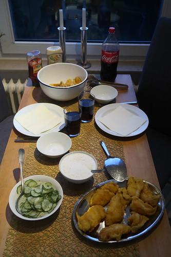 Backfisch mit Joghurtdip, Gurkensalat und frittierten Kartoffelspalten (Tischbild)