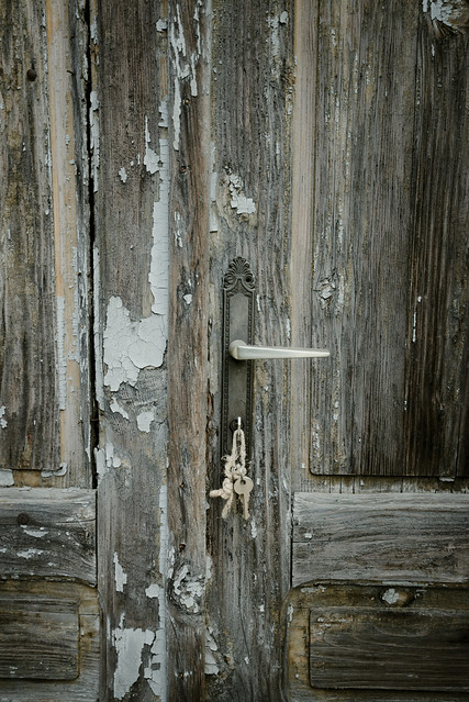 Old wooden door with the keys inside the keyhole.