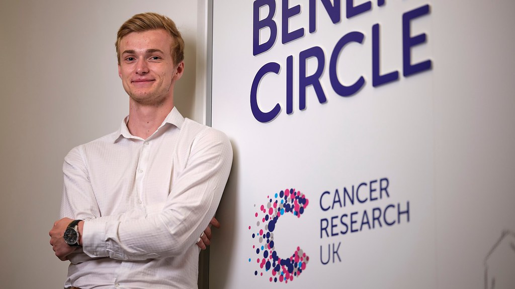 Student standing in front of a Cancer Research UK sign