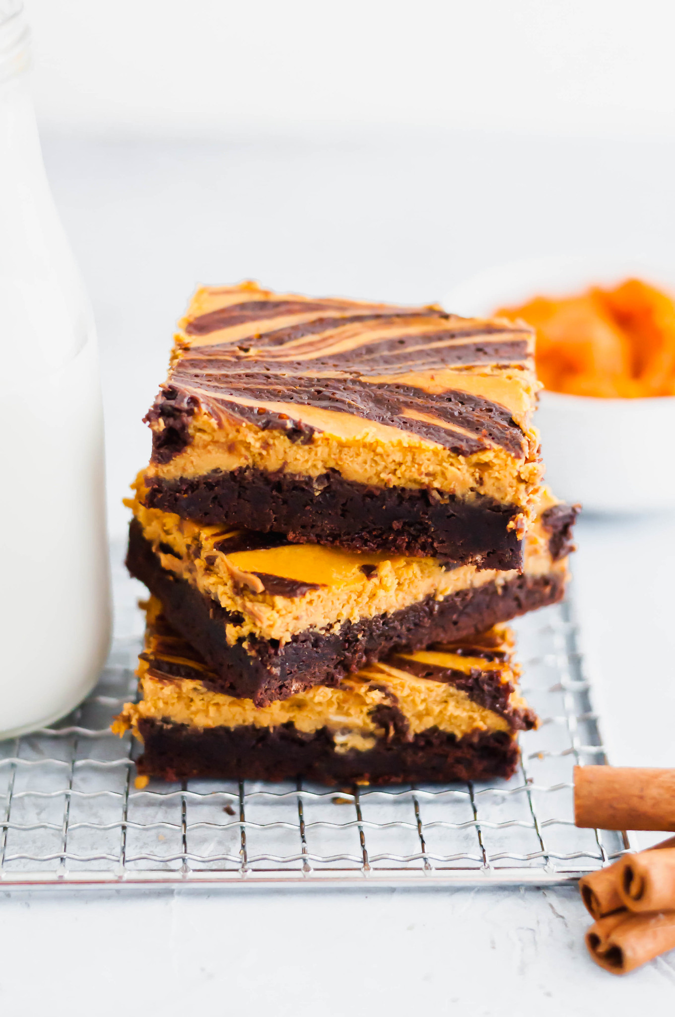These Pumpkin Cheesecake Brownies are a must try dessert this fall. Thick, fudgy one pot brownies topped with a simple, delicious spiced pumpkin cheesecake. Fall perfection.