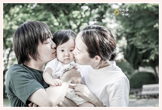 家族の写真 パパとママが娘さんにキス 公園にて