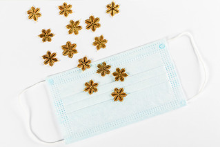 Golden snowflakes scattered on medical mask and white background | by wuestenigel