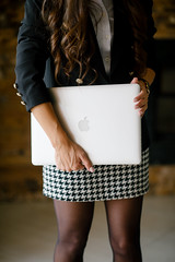 Young woman in pepito suit and vintage coat holding a laptop in her office.