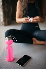 Bottle of water and smartphone closeup with fitness girl background.