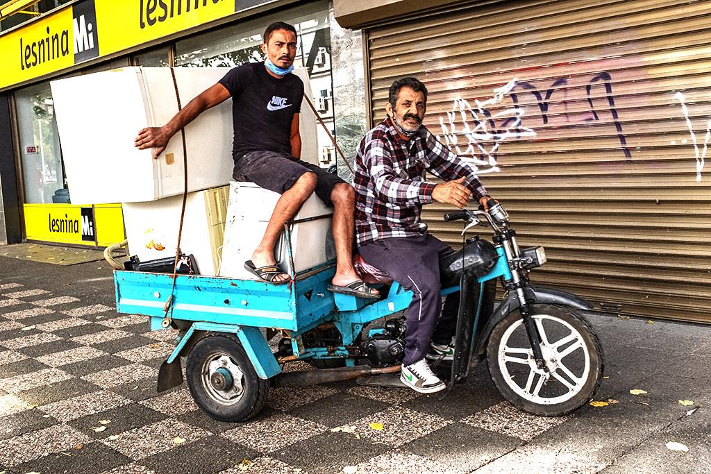 Two men on three-wheeled truck on sidewalk on 9-27-20--Skopje