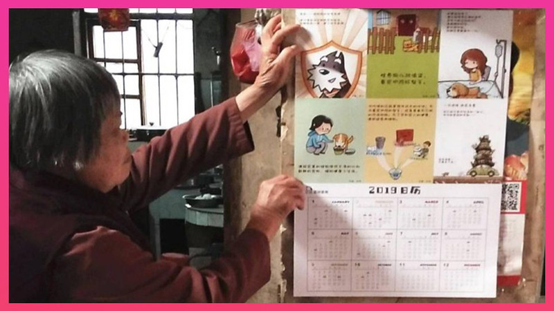 A woman in a rural village displays a calendar distributed by Animals Asia on preventing rabies