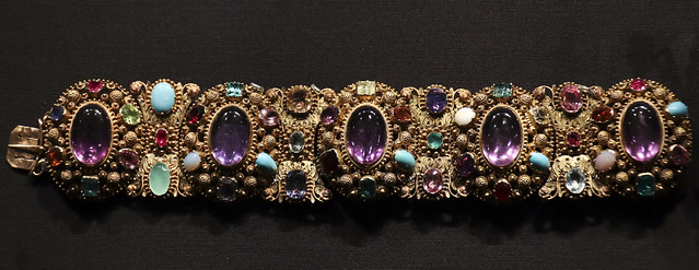 Locket bracelet, France, about 1820-30, Three colours of gold, with cannetille and grainti decoration, set with central amethysts and various faceted and cabochon gemstones