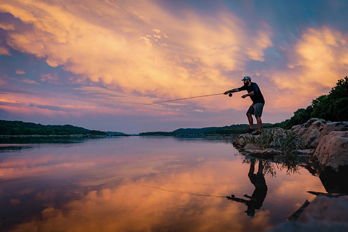 Photo of angler fly fishing on a riverbank