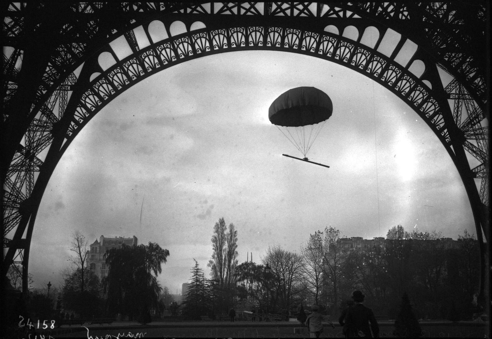 1912. Испытания парашюта М. Майу. Спуск парашюта, прикрепленного к 40-килограммовой балке. Вид из-под Эйфелевой башней. 20 октября