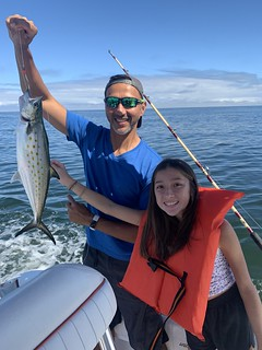Photo of father and daughter holding a Spanish mackerel