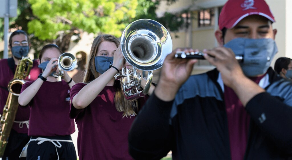 Collegiate band musicians playing instruments while wearing custom-made masks