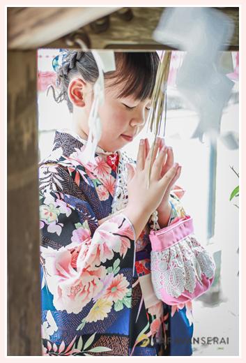 七五三 神社で祈りを捧げる7歳の女の子