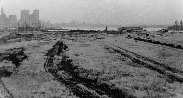 Going nowhere fast. Remnants of the Central Railroad of New Jersey tracks being overtaken by hardy reeds and other plants. A crane graveyard and the skyline of Lower Manhattan loom in the background. Jersey City. March 1976.
