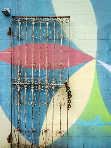 A rusted gate opened up against a colourful mural in Vancouver, Canada