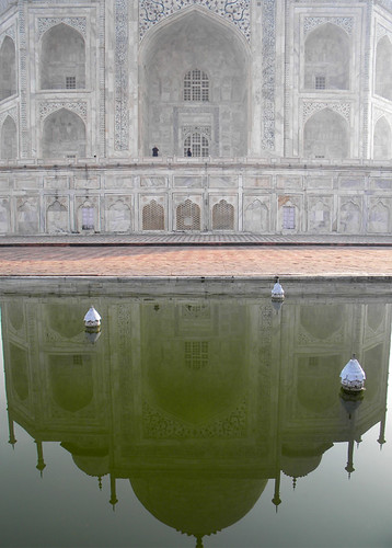 The marble facade of the Taj Mahal mirrored in the reflecting pool (Agra, India)