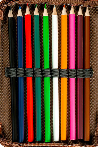 Sharpened colored pencils in a pencil case, top view | by wuestenigel