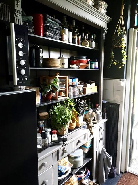 Open keukenkast met serviesgoed bestek en theedoeken