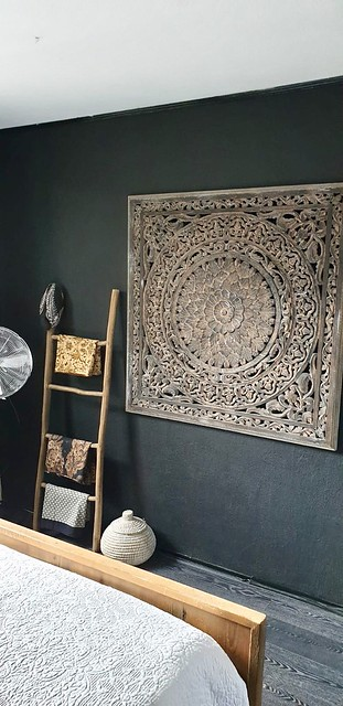 Groot ornament aan de zwarte muur slaapkamer