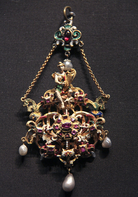 Pendant with a muse playing a harp, Germany, about 1600-20, enamelled gold with silver, rubies, garnet and pearls