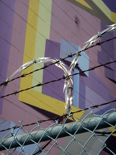 Soft pinks and purples of an industrial mural adorned with razor wire in Vancouver, Canada