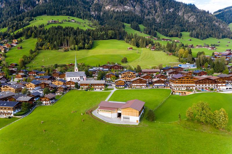 Alpenlandschaft von oben mit grünen Hügeln, Holzhäusern, Kühen und einer Kirche