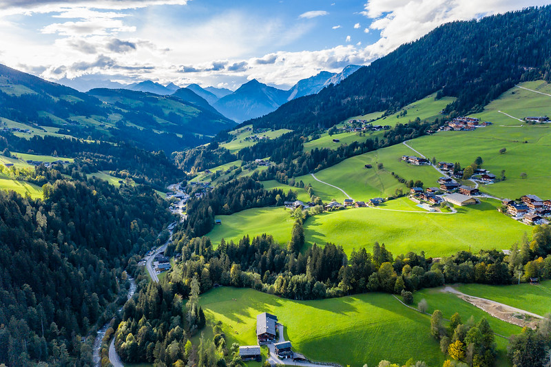 Alpenlandschaft mit grünen Hügeln, Ferienhäusern, Wäldern und riesigen Berggipfeln im Hintergrund