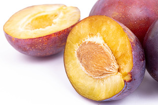 Macro of sliced Plums above white background