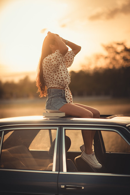 Young woman sitting on car top at sunset.
