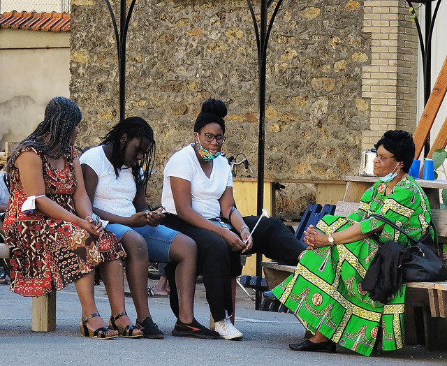 Black women conversing lively in their new Public Housing