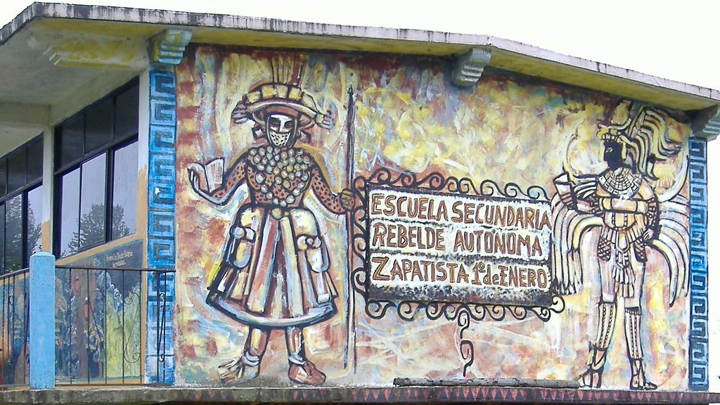 The side of a school painted with a bright mural with the name of the school written in Spanish