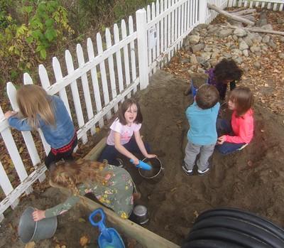 sandbox full of children who are full of sand