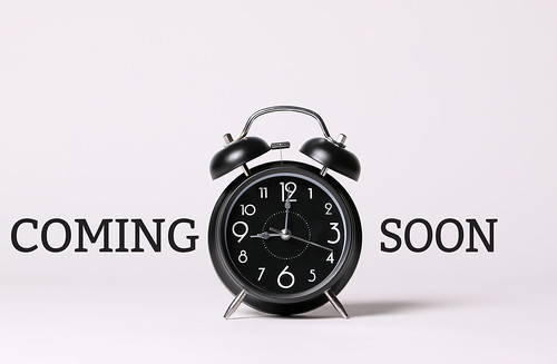 Coming soon text and black alarm clock on a white background | by focusonmore.com