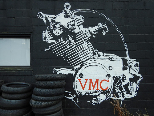 white machine 'mouse' on a black wall accompanied by tires