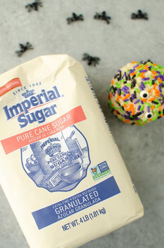 Sugar cookies covered in Halloween sprinkles; next to a bag of sugar
