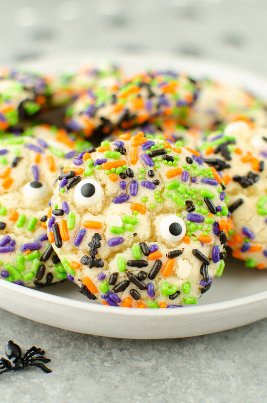 Sugar cookies covered in Halloween sprinkles on a white plate