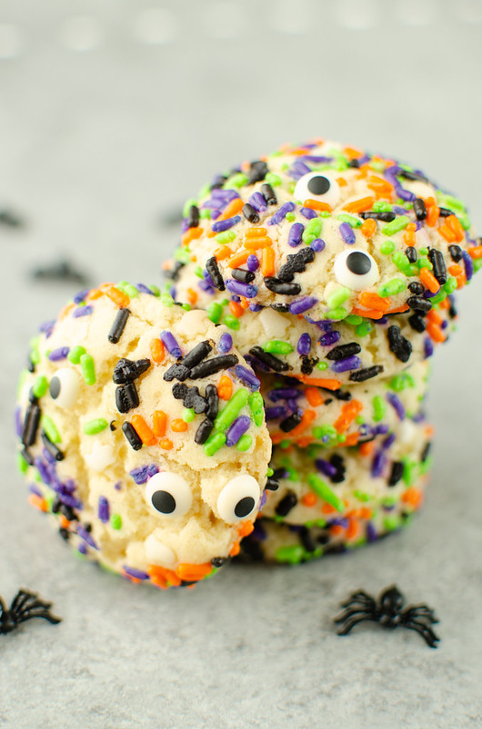 Sugar cookies with Halloween sprinkles in a stack with plastic spiders as decoration