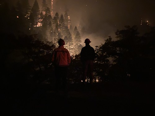 Photo of two firefighters against backdrop of a forest fire