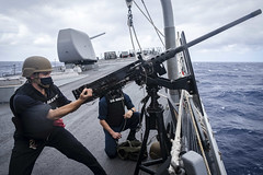 In this file photo, Fire Controlman 2nd Class Samuel Thomas 'racks' an M2HB .50-caliber machine gun during a small craft attack team (SCAT) drill in the South China Sea aboard USS John S. McCain (DDG 56), Oct. 7. (U.S. Navy/MC2 Marc Castaneda)