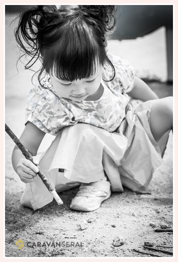 公園の砂場で絵を描く女の子 モノクロ写真