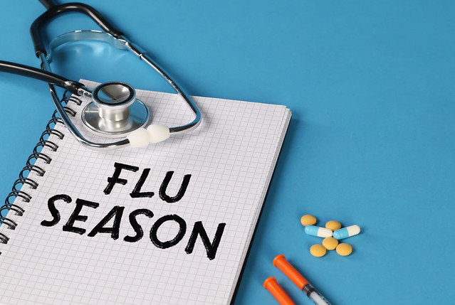 Flu Season written on spiral notepad with stethoscope, syringe and pills on blue background