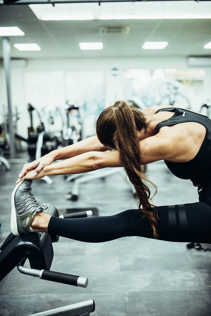 Woman with a pony tail stretching her glutes and hamstrings in the gym.