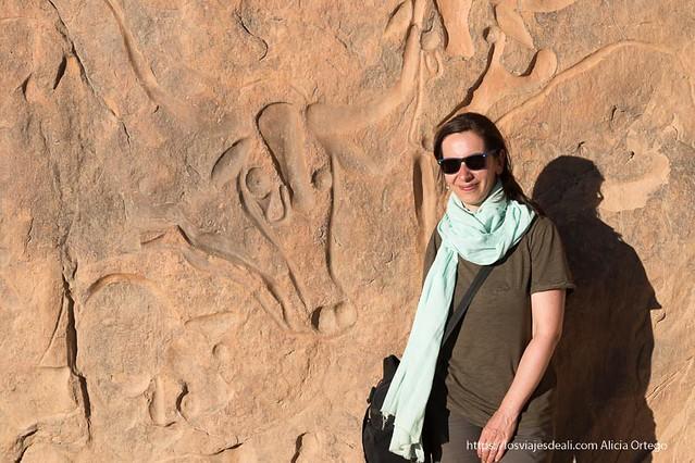 Alicia Ortego en el desierto de Argelia ante un petroglifo
