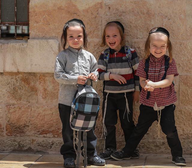 Three excited, a bit anxious, a bit joyful young Ultra-Orthodox Jewish boys